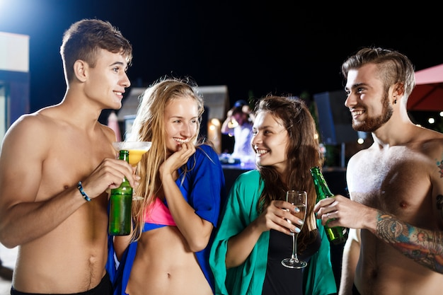 Cheerful friends smiling, rejoicing, resting at party near swimming pool