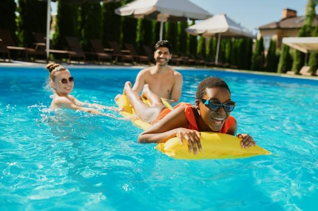 Cheerful friends swim on a mattress in the pool