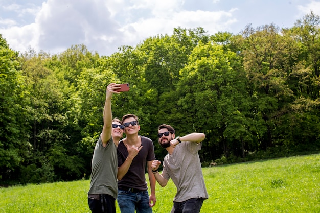 Cheerful friends taking selfie on glade