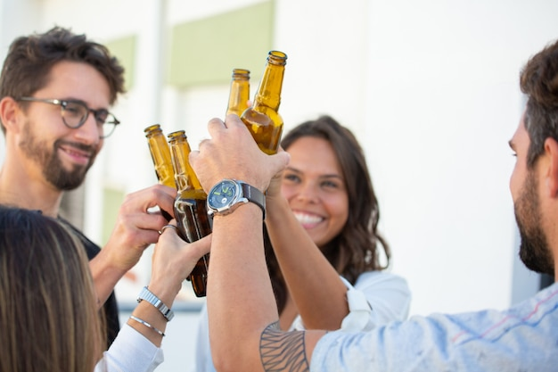 Cheerful friends toasting beer and celebrating success