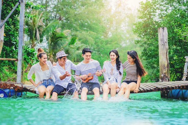 Cheerful friends together travelling, sitting at small bridge let playing guitar