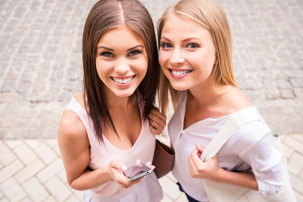 쾌활한 친구. 야외에서 서로 가까이 서 있는 동안 카메라를 보며 웃고 있는 두 아름다운 젊은 여성의 상위 뷰