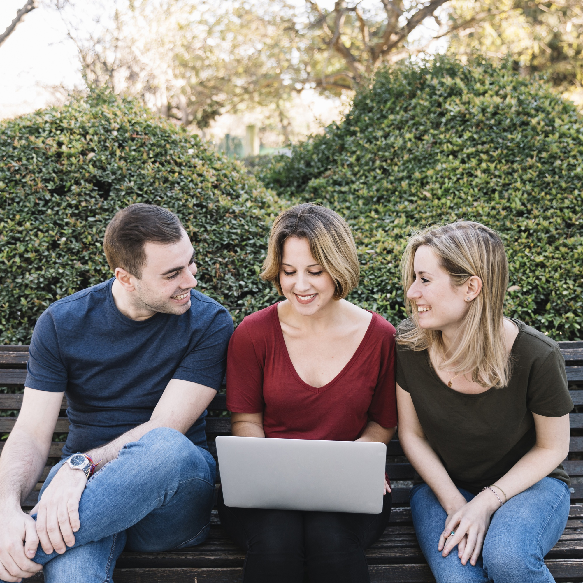 Cheerful friends using laptop in park
