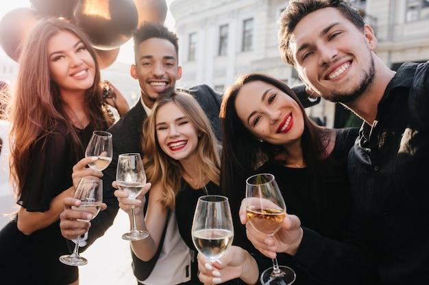 Веселые друзья с большими улыбками фотографируются во время праздника