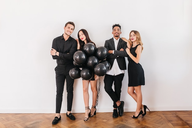 Cheerful friends with black balloons during home party