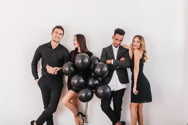 Веселые друзья с черными воздушными шарами во время домашней вечеринки