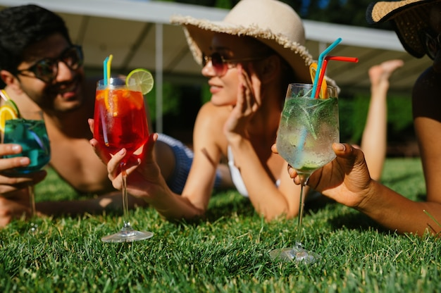 Cheerful friends with coctails rest on the grass near the pool. happy people having fun on summer vacations, holiday party at the poolside outdoors. one man and two women are sunbathing
