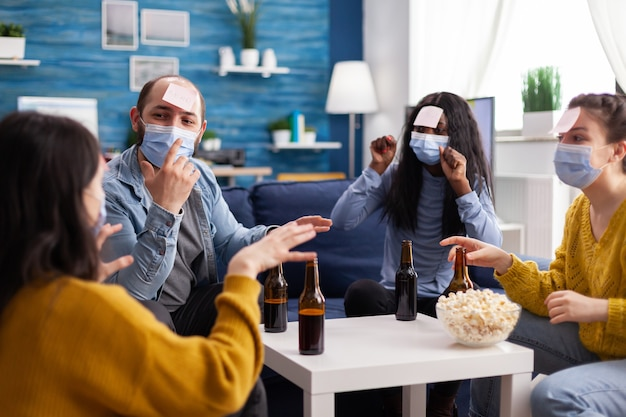 Cheerful friends with sticky notes on foreheads playing name game with beer popcron keeping social distacing with face mask to prevent spread of covid19 in home living room. conceputal image.