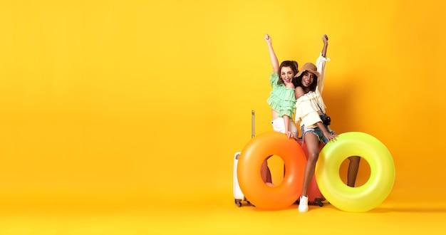 Веселые друзья женщина, одетая в летнюю одежду, сидит на чемодане и резиновом кольце на желтой стене копией пространства.