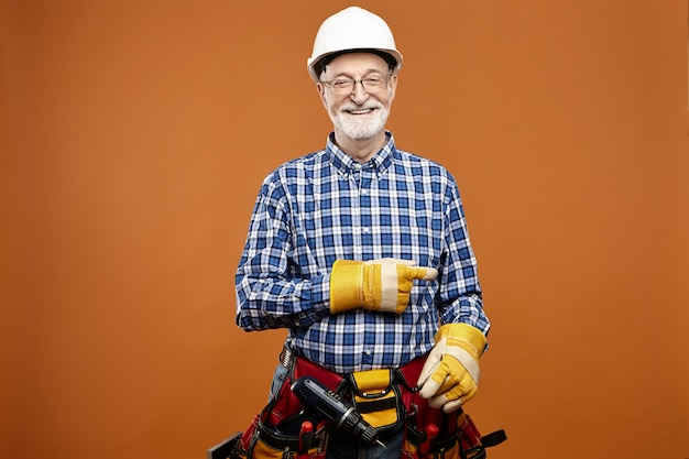 Cheerful frinedly looking caucasian senior male carpenter pointing index finger carrying working equipment around waist. smiling elderly bearded electrician posing in protection gloves and tool belt
