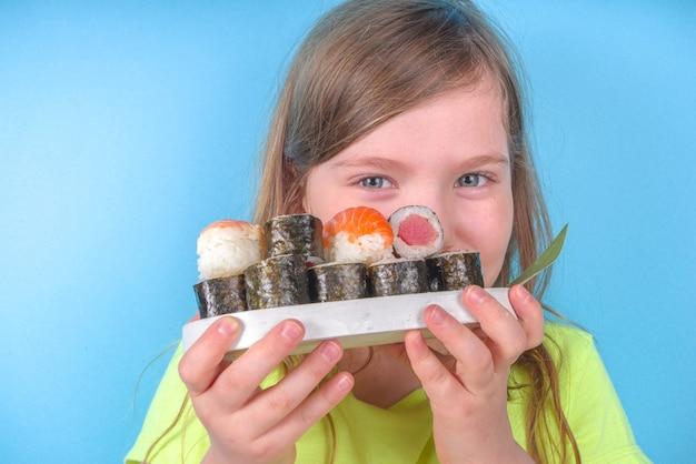 다양 한 스시 롤과 젓가락으로 쾌활 한 재미있는 백인 금발 유치원 아이 소녀. 밝은 파란색 벽에