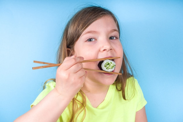 Cheerful funny caucasian blond preschool child girl with various sushi roll and chopsticks. on bright blue wall
