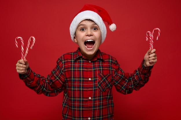 Веселый забавный ребенок мальчик, красивый ребенок позирует на цветном красном фоне с рождественскими леденцами, сладкими полосатыми леденцами в руках, радуется, глядя в камеру. новогодняя концепция с копией пространства