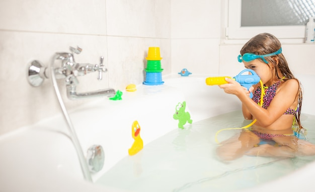 Cheerful funny girl in blue water glasses is playing with a water gun while sitting in a bathroom with water and bright toys