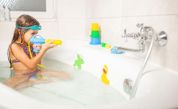 푸른 물 안경에 쾌활한 재미 있은 소녀는 물과 밝은 장난감으로 욕실에 앉아있는 동안 물총을 가지고 노는