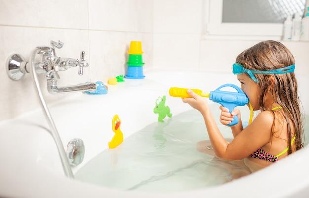 Веселая смешная девочка в голубых очках с водой играет с водяным пистолетом