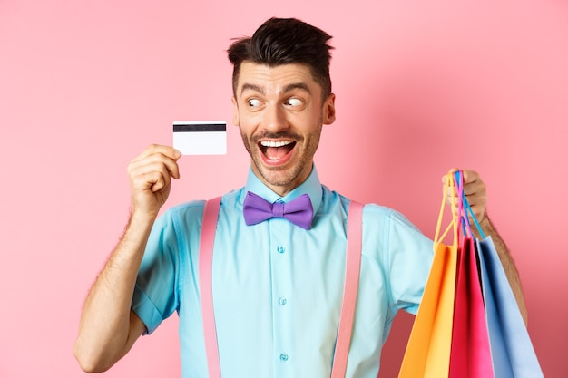 Cheerful funny guy looking at plastic credit card and smiling, buying gifts, holding shopping bags, standing on pink.
