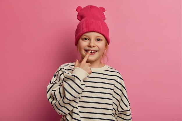 Cheerful funny little girl points at her teeth, cares about oral hygiene, dressed in fashionable clothes, has healthy skin, boasts of adult tooth to friends on playground, isolated on pink pastel wall