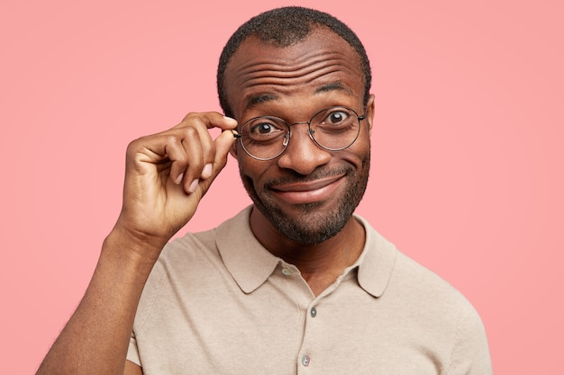 Cheerful funny man hears interesting merry story from interlocutor, looks positively through eyewear