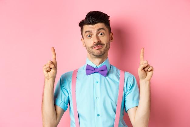 Веселый смешной человек в галстуке-бабочке указывая пальцами вверх, показывая рекламу и нерешительно улыбаясь, стоя над розовым. копировать пространство