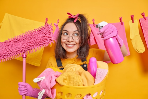 Cheerful funny millennial girl wears round spectacles and rubber gloves poses with cleaning supplies does laundry at home poses against clothesline hanging over yellow wall