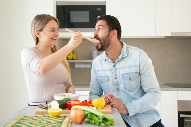 Cheerful funny young couple cooking dinner together, cutting fresh vegetables on in kitchen. woman giving slice of food on big spoon to her boyfriend to taste. family cooking concept