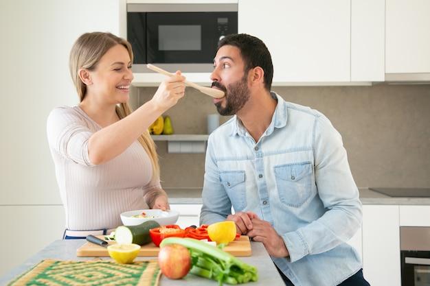 陽気な面白い若いカップルが一緒に夕食を作って、キッチンで新鮮な野菜をカットします。彼女のボーイフレンドに大きなスプーンで食べ物のスライスを与えて味わう女性。家族の料理のコンセプト