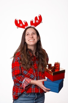 Cheerful funny young woman in checkered shirt with red deer antlers holds a christmas gifts and laughing