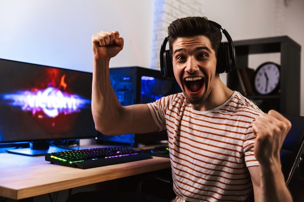 Cheerful gamer playing video games on computer and rejoices