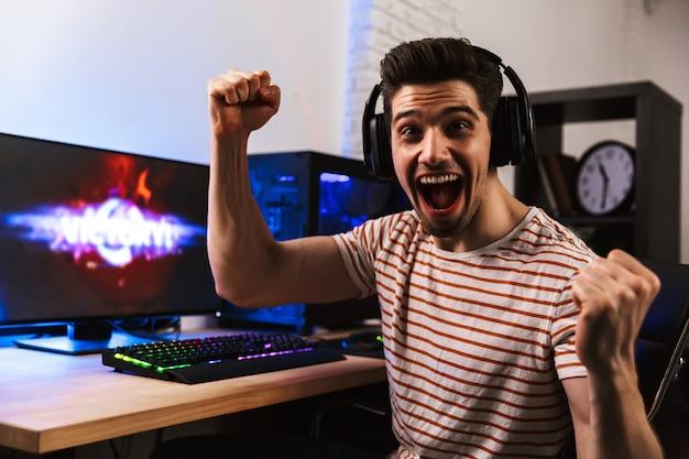 Веселый геймер играет в видеоигры на компьютере и радуется
