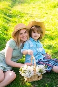 庭でピクニック中に座っている陽気な庭師の家族。晴れた日にリラックスした若い笑顔の家族。