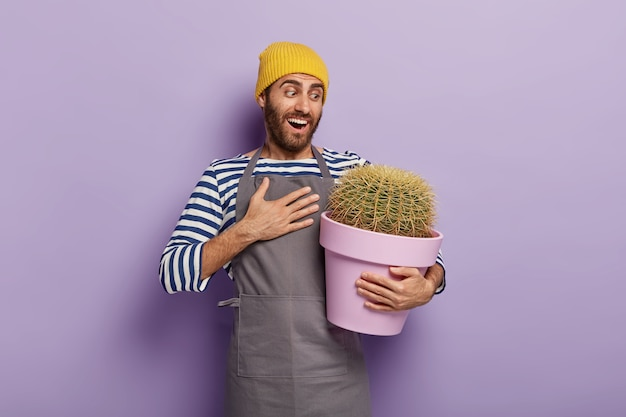 Cheerful gardener posing with a big  potted cactus
