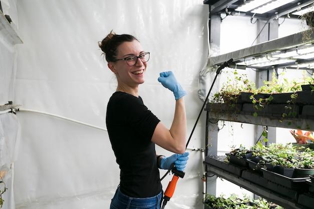 Веселый садовник, демонстрирующий бицепс в теплице