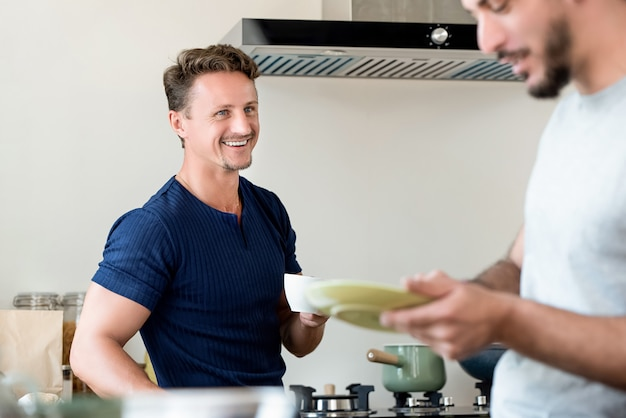 Cheerful gay couple preparing breakfast in kitchen at home