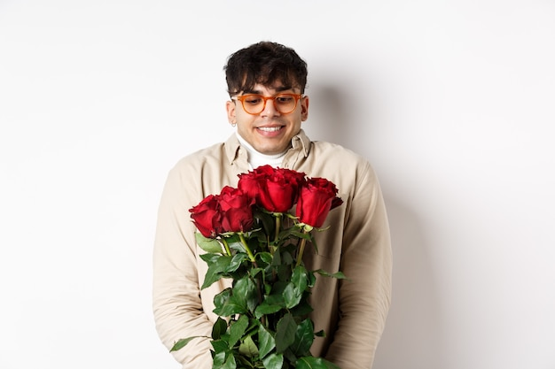Cheerful gay man receive red roses from boyfriend, looking excited and smiling, having romantic date on valentines day with lover, standing over white background.