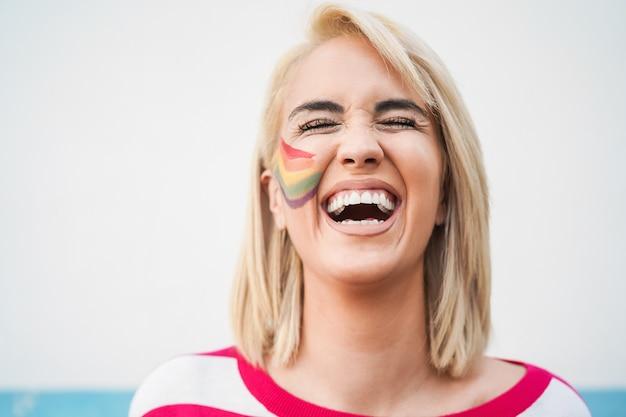 Веселая гей-женщина смеется на открытом воздухе на параде лгбт