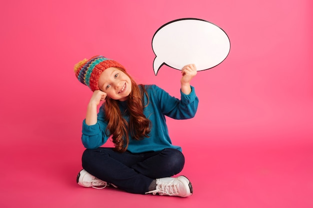 Cheerful ginger girl holding bubble speech and looking camera