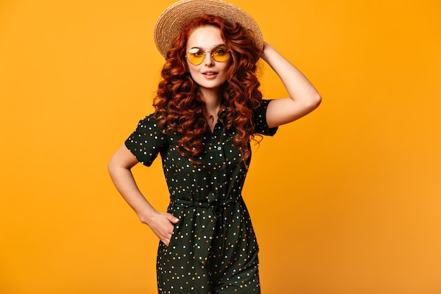 Cheerful ginger girl in sunglasses posing with hand in pocket. studio shot of refined caucasian lady in straw hat isolated on yellow background.