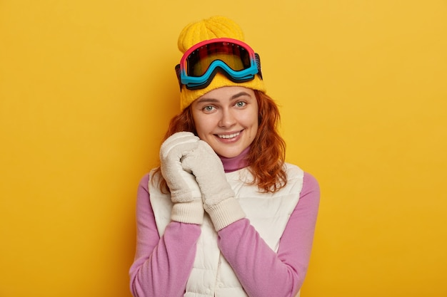Cheerful ginger woman keeps both hands near face, smiles gently, wears ski goggles, dressed in warm clothes, isolated over yellow studio wall