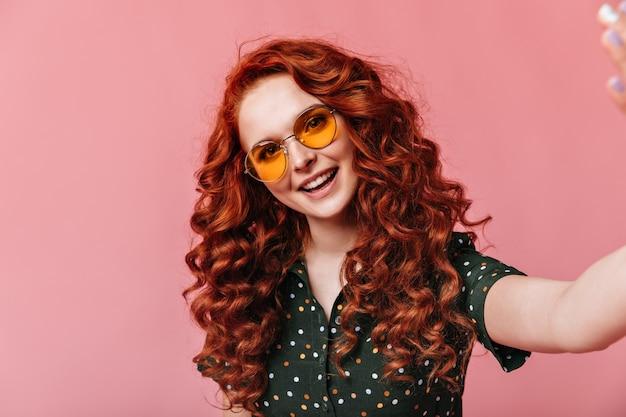 セルフィーを取る陽気な生姜の女性。ピンクの背景にポーズをとるサングラスの好奇心旺盛な巻き毛の少女のスタジオショット。