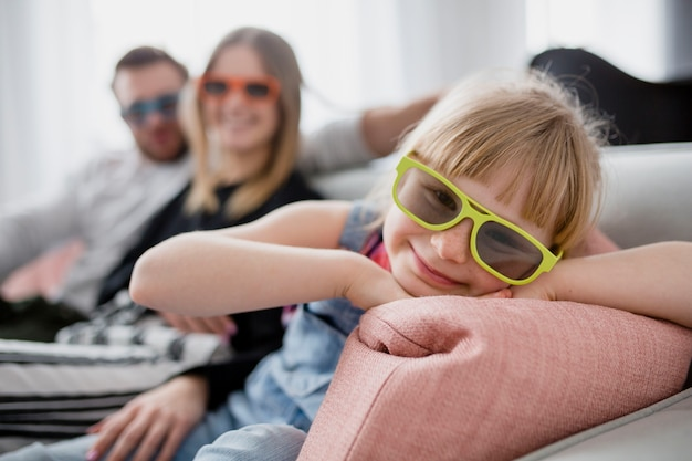 Cheerful girl in 3d glasses near parents