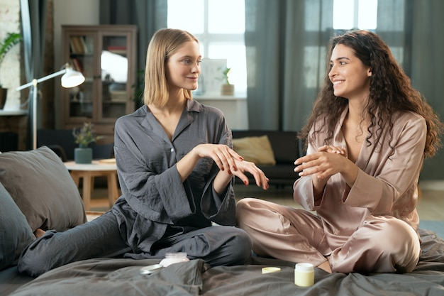 朝、ベッドに座って天然の手作り化粧品を塗る元気な女の子、スマートフォンを持った友達がカメラで彼女を撮影
