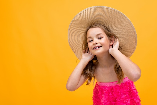 Cheerful girl in a beach hat on an orange background, holds hands by the ears and listens carefully