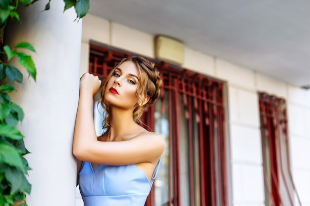 Cheerful girl in a blue dress with red lips and a stylish hairdo