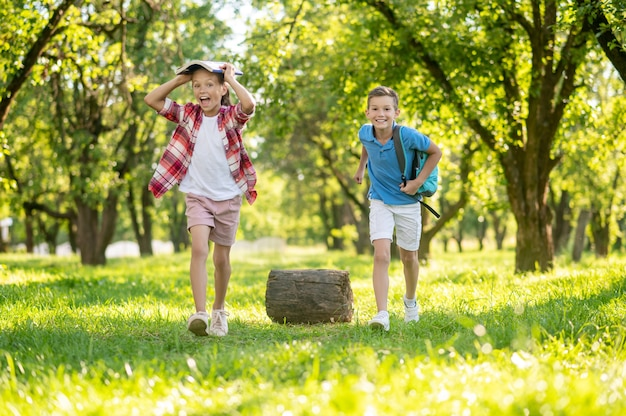 Cheerful girl and boy with backpack in park