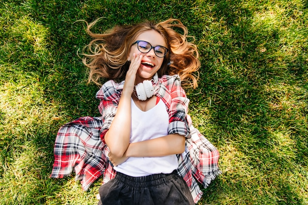 Cheerful girl in casual outfit posing in park. overhead shot of laughing merry lady lying on grass.