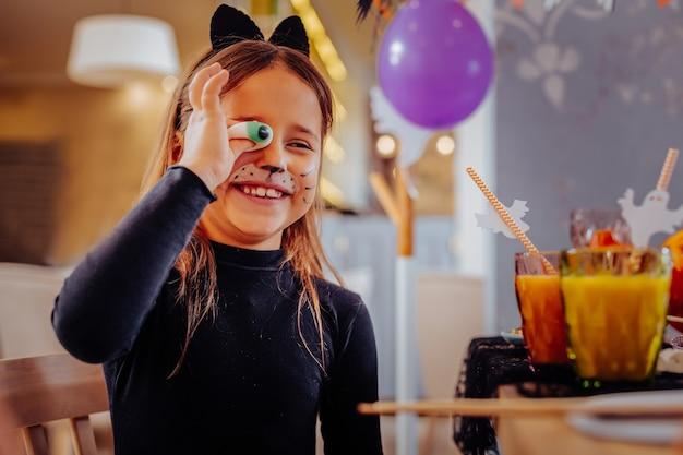 명랑 소녀. 할로윈을 축하하면서 넓게 거미 눈을 잡고 웃고 고양이 양복을 입고 쾌활한 검은 머리 소녀
