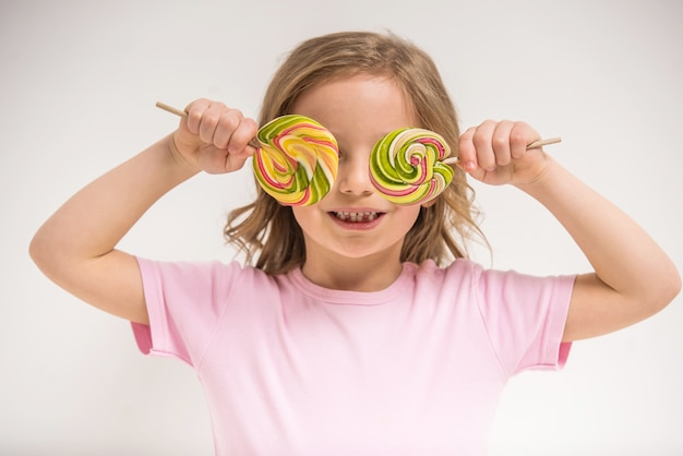 Cheerful girl covering eyes with lollipops and smiling.