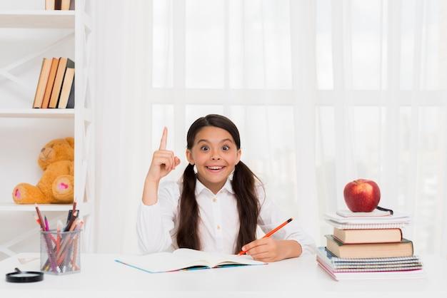 Cheerful girl doing homework with joy