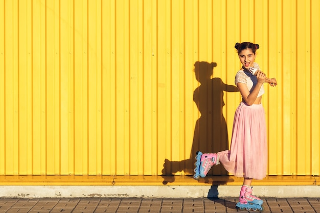 A cheerful girl eats ice cream and rolls on rollers in summer against a yellow wall.